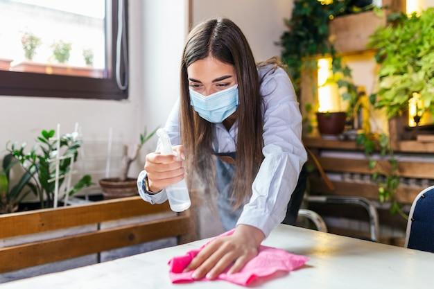 다음 고객을 위해 레스토랑이나 카페에서 테이블을 소독하는 동안 보호 마스크를 착용 한 웨이트리스. 코로나 바이러스 및 중소기업이 작업 개념에 열려 있습니다. 프리미엄 사진