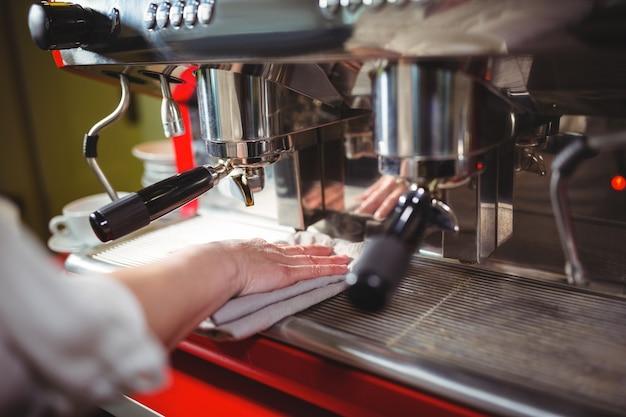 Официантка вытирая кофемашину с салфеткой в кафе