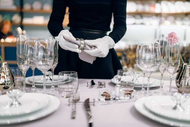 Waitress with a bottle of champagne, table setting