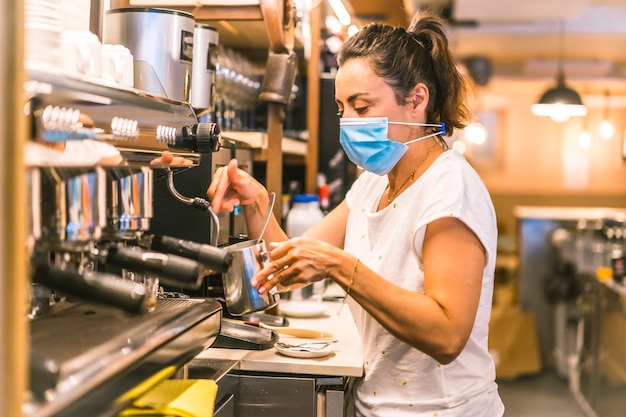 A waitress with a face mask in a bar. making a coffee with milk with the coffee machine one spring morning
