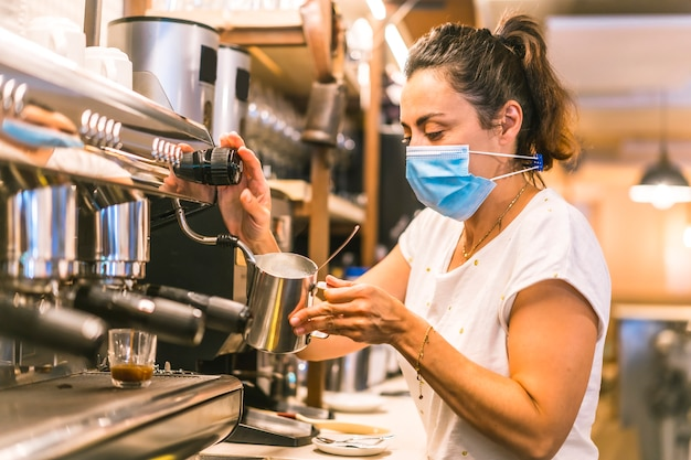 A waitress with a face mask in a bar. preparing a coffee