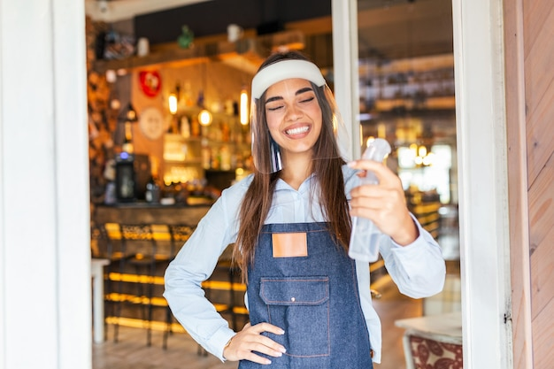 Waitress with face shield greeting customers