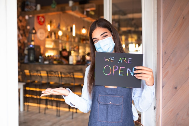Waitress with protective face mask holding open sign