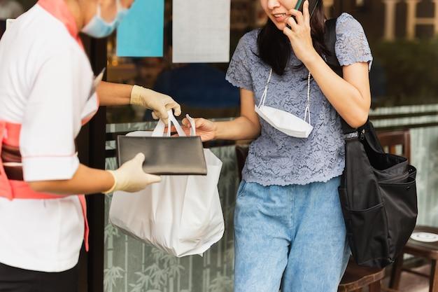 여자 고객에게 음식 가방을 꺼내주는 보호 마스크가있는 웨이트리스.