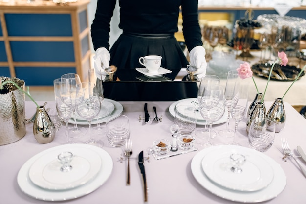 Waitress with tray puts the dishes, table setting