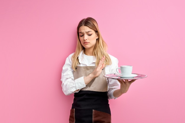Официантка держит поднос с чашкой на изолированном розовом фоне с отрицательным знаком, показывающим неприязнь