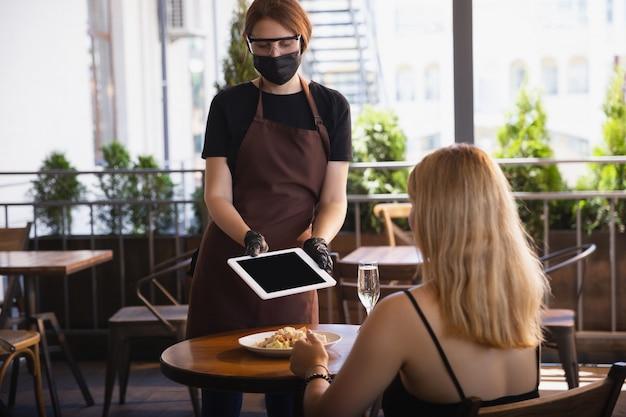 La cameriera lavora in un ristorante con una mascherina medica, guanti durante la pandemia di coronavirus