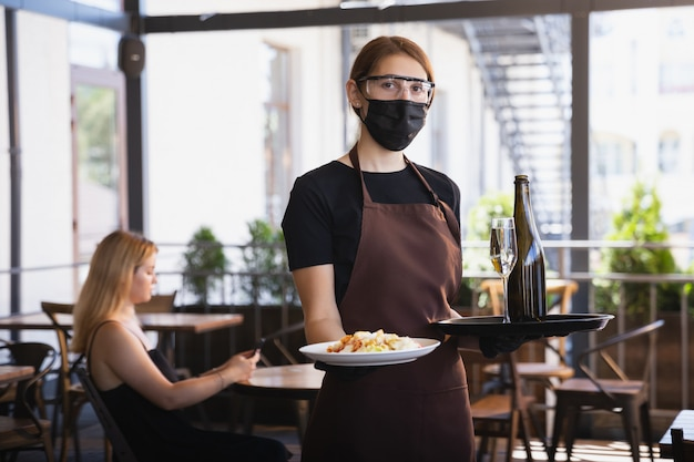 Waitress works in a restaurant in a medical mask, gloves during coronavirus pandemic