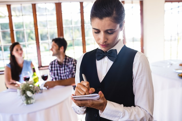 Waitress writing order on notepad in restaurant
