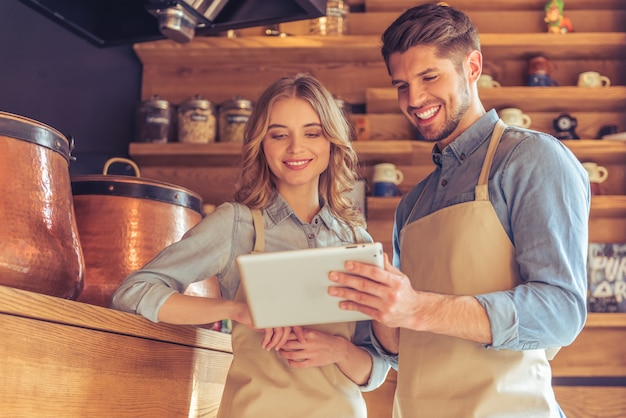 Waitress and young waiter in aprons are using a tablet.