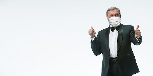 あなたを待っています。白い背景の上の保護フェイスマスクで優雅な年配の男性ウェイター。チラシ、コピースペース。カフェ、レストランオープン。コロナウイルスパンデミック時の安全性。ゲスト、クライアントの世話をします。