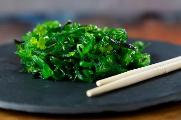 검은 접시와 나무 테이블에 참깨를 곁들인 미역 샐러드