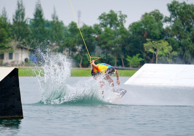Wake boarding rider jumping trick with water splash in wake park.
