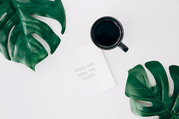 Wake and smell the coffee message on note near the coffee and monstera leaves on white desk
