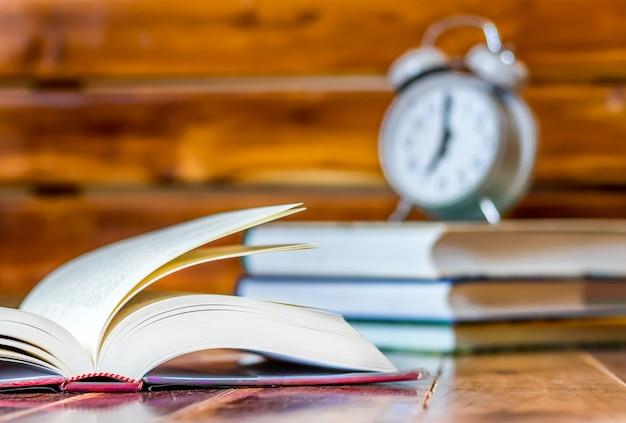 일출과 나무 테이블에 알람 및 독서 책을 깨워