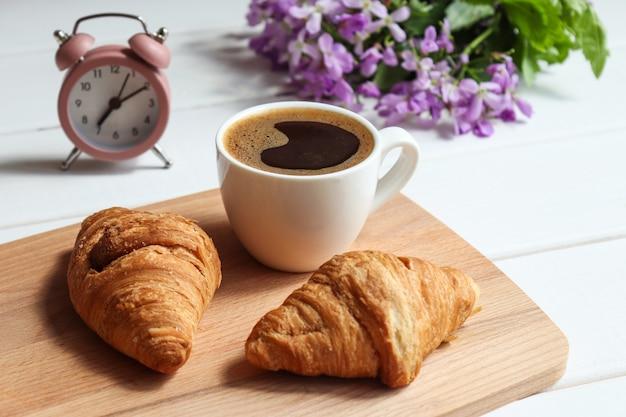 Просыпайтесь и концепция доброго утра кофе с круассанами будильник и цветы на столе