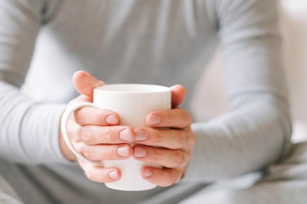 Просыпайся напитком. человек сидит и держит белую чашку горячего утреннего чая.
