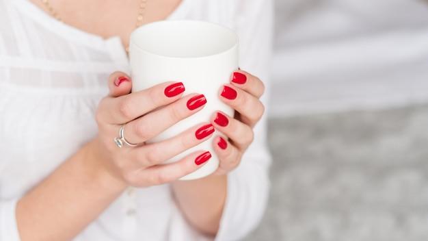 飲み物を起こします。女性は熱い朝の飲み物の白いカップで手を手入れしました。