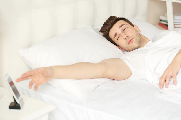 ウェイクアップコンセプト。若い男は目覚ましで目を覚ます。