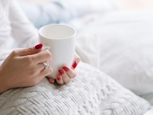 飲み物を起こします。熱い朝の飲み物の白いカップと女性の手。