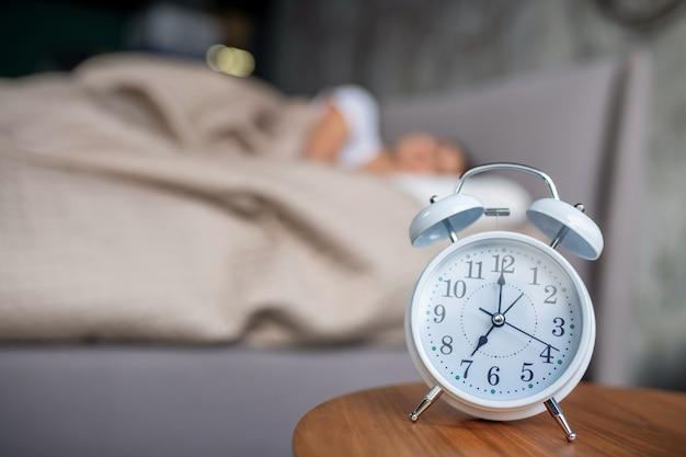 Просыпаться. белый механический будильник стоит возле кровати