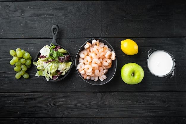 Набор ингредиентов салата из вальдорфских креветок, с яблочным соусом и виноградом, на черном деревянном столе