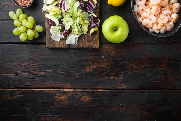 Набор ингредиентов салата из вальдорфских креветок, с яблочным соусом и виноградом, на старом темном деревянном столе, плоская планировка, вид сверху