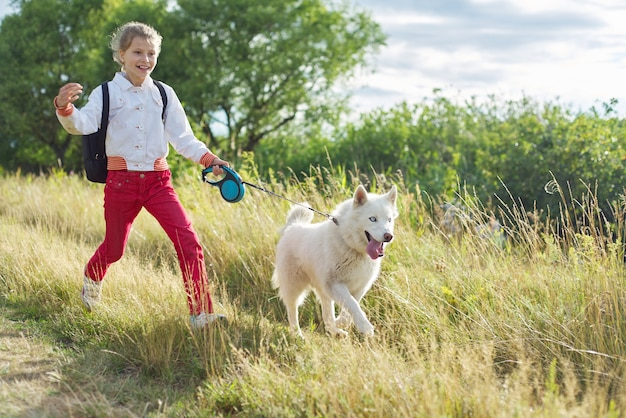 Walk girl with dog in nature, run child with pet in sunny meadow. active healthy lifestyle, walking with dog, friendship of child with animal