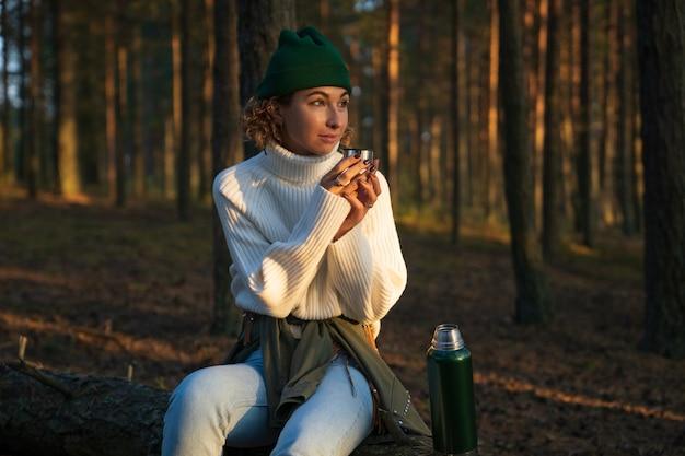 秋の森の中を歩く若い女性は、魔法瓶から熱い飲み物を飲みながら倒れた木の上に座ってリラックス