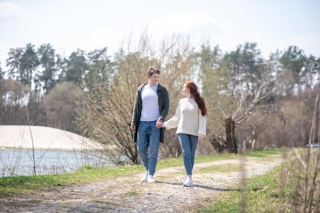 自然の中を歩きます。晴れた春の日に自然の中を歩いて手をつないできれいな女性を見て喜んで気配りのある男