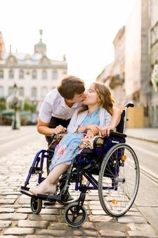 Прогулка по городу. веселая девушка в инвалидной коляске целуется со своим красивым парнем, проводя время в любви вместе