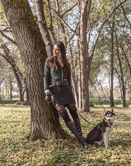 Прогулка по октябрьскому парку у ствола дерева стоит молодая женщина с домашним питомцем хаски на поводке.