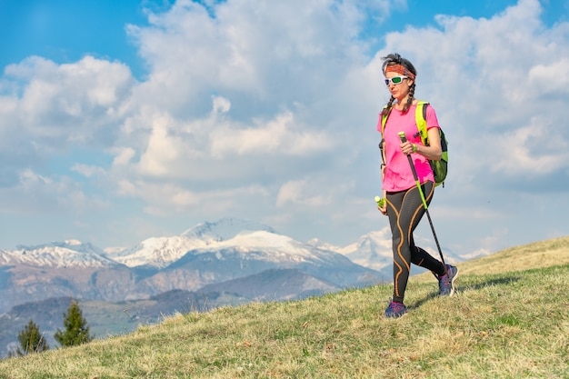 雪山を背景に春の山の牧草地を歩く