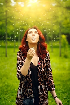Walk in the park. young teenager girl with red hairs blow to dandelion flower.