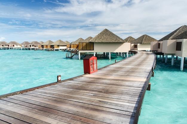 Walk way to water villa on crystal clear water at island