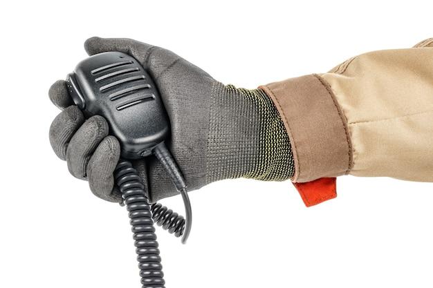 Портативный микрофон для рации со спиральным соединительным шнуром в мужской руке в черной защитной перчатке и коричневой униформе на белом