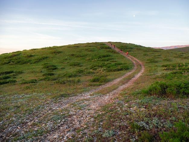 早朝の山脈のウォーキングやハイキングコース。広大な緑の谷の素晴らしい景色を眺めながら、狭い山道をハイキングしましょう。