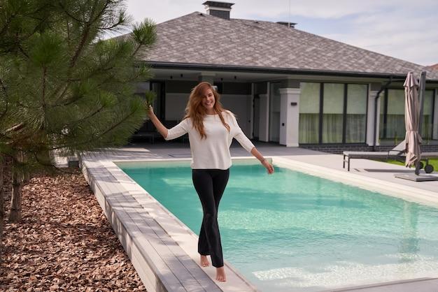 아침에 산책. 그녀의 수영장 근처를 걷고 큰 소리로 웃는 생강 소녀의 전체 길이 보기. 여름 컨셉
