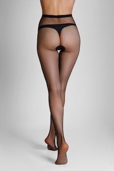 Walking away long slim female legs in black fishnet tights. back view.