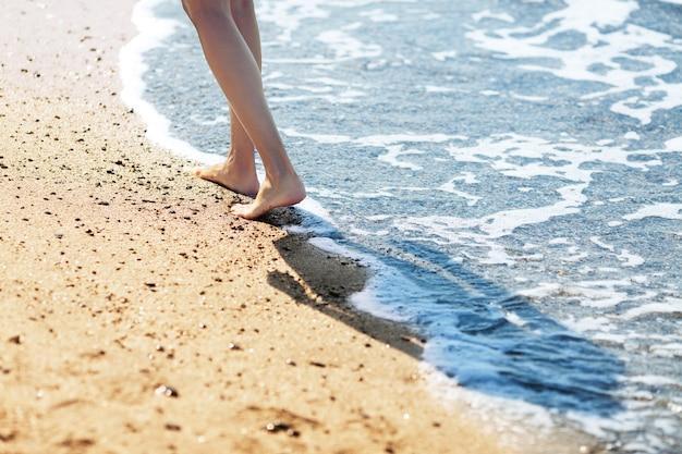 砂浜でサーフィンに沿って裸足で歩く