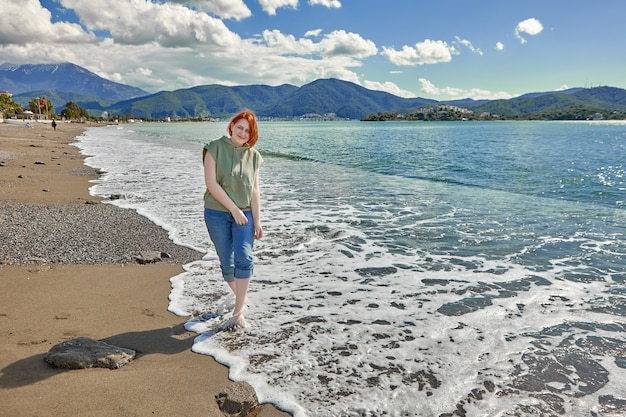 Молодая европейка гуляет босиком по мокрому пляжному песку по линии прибоя у моря