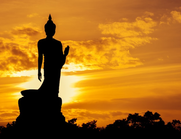 Walking buddha statue silhouette at sunset