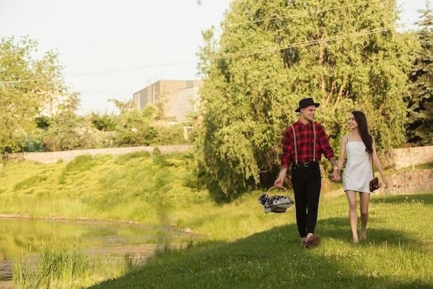 歩いて。夏の日に公園で一緒に週末を楽しんでいる白人の若くて幸せなカップル