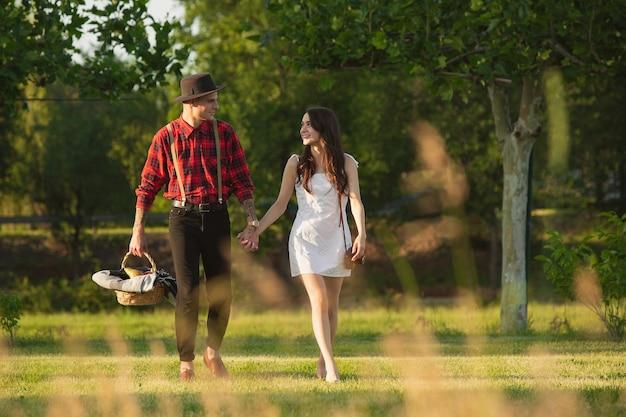 아래로 걸어. 여름날 공원에서 함께 주말을 즐기는 백인 젊고 행복한 커플