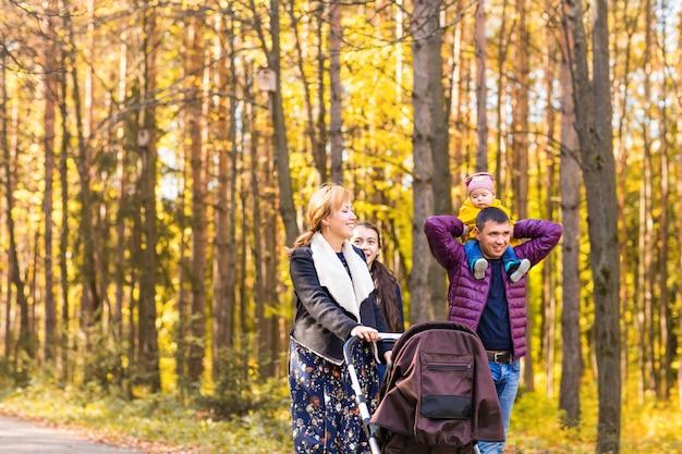 Гуляющая семья с двумя детьми в осеннем парке.