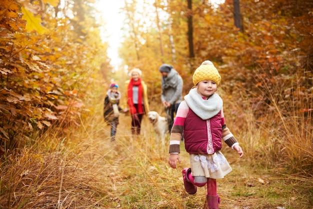 秋の森の中を歩く女の子と家族