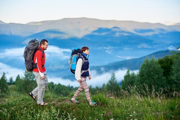 Прогулка в горах. парень и девушка с рюкзаками идут по дорожке на вершине холма с прекрасным пейзажем гор в дымке. концепция активного отдыха на природе