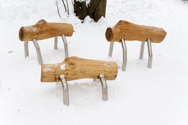 Прогулочные бревна. интересные скамейки в виде необычных животных из дерева на снегу. скамейки в виде овец. зимний пейзаж.