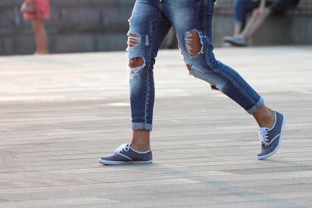 Walking man in ripped jeans