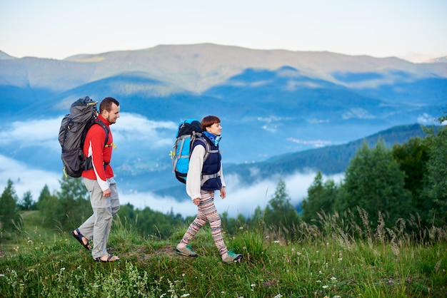 Walking in the mountains. the guy and the girl with backpacks are on the path on a hilltop with a beautiful landscape of mountains in the haze. concept of active outdoor hiking lifestyle